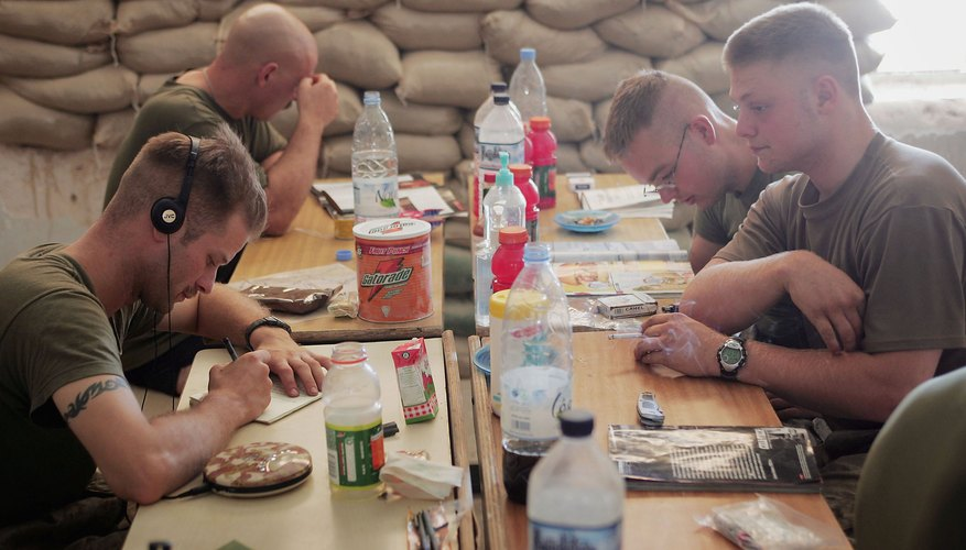 U.S. Marines read and write letters during a break in their barracks in Iraq.