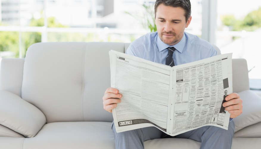 Man reading newspaper on couch