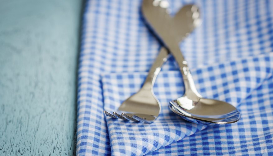 A spoon and fork on a blue tablecloth.