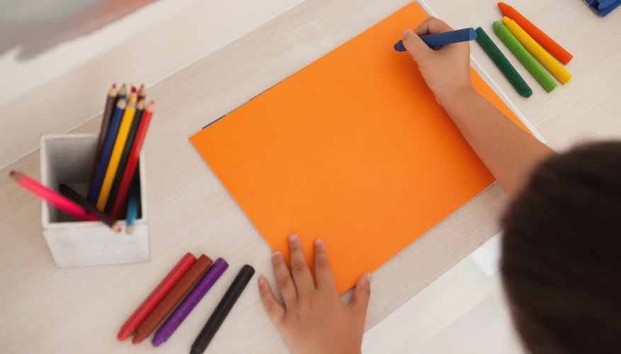 An overhead view of a boy creating with paper and colored pencils.