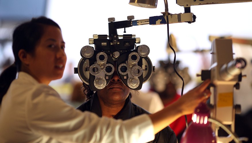 An optometrist performs an eye exam on a patient in a dim exam room.
