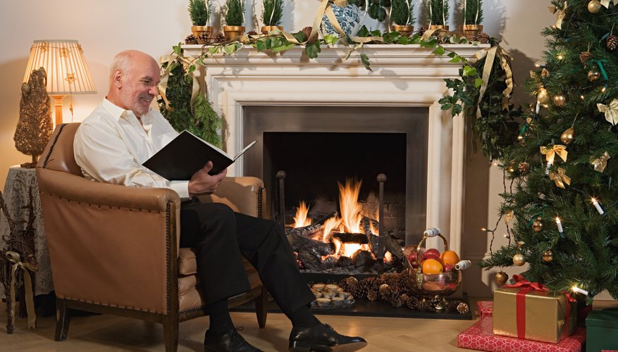 A man reading a novel by his Christmas Tree.