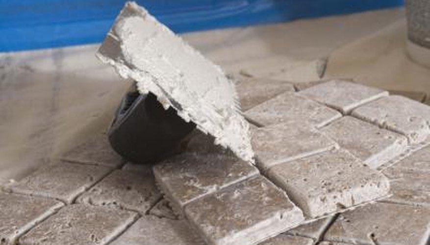 Cover a plastic flower pot with tile grout to make a mosaic on the pot.