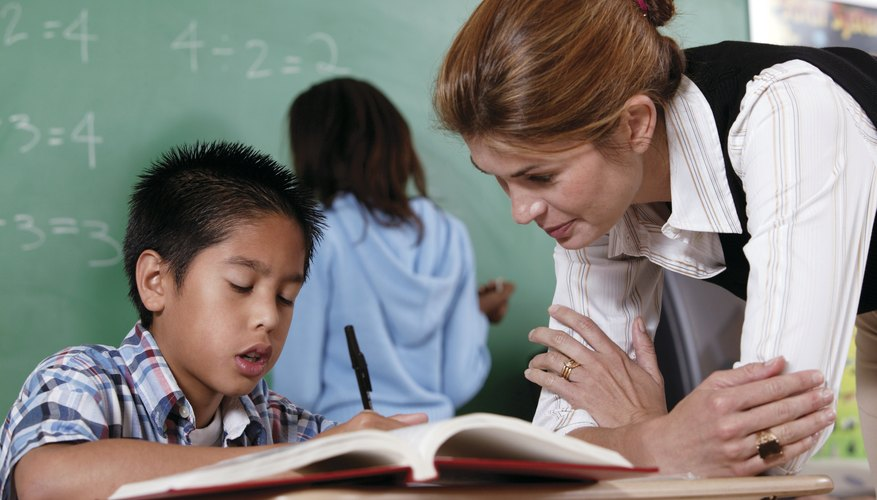 Teacher help young student with workbook in classroom