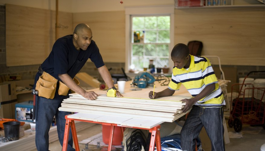Two young kids and a man are doing woodworking together.