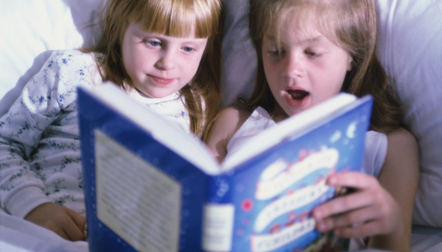 Young children are looking through a picture book.