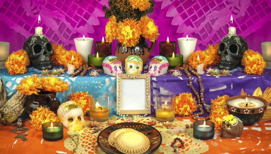Day of the Dead altar with flowers, candles and skulls