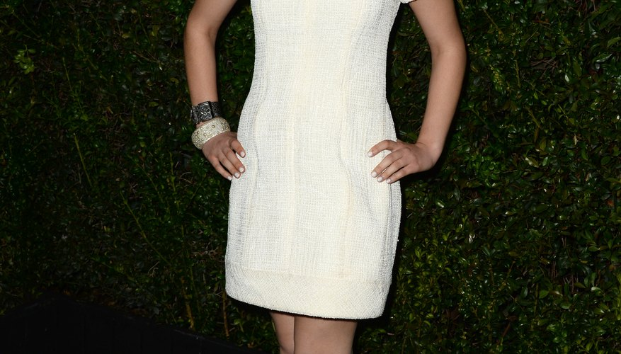 Actress Odeya Rush pairs a simple white dress with several bangles.