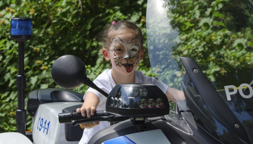 A young girl with her face painted climbing onto a policeman's motorcycle.