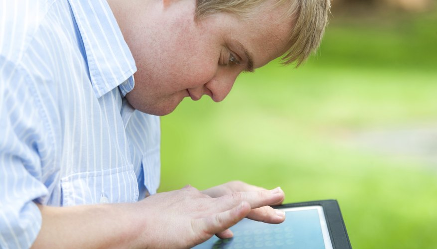 A boy with down syndrome is using a tablet.