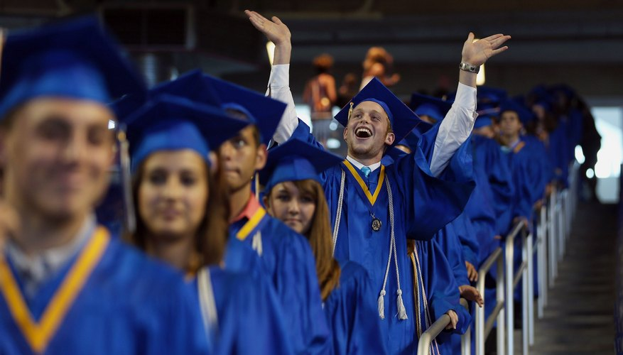 An excited graduate raising his arms to the crowd at commencements.