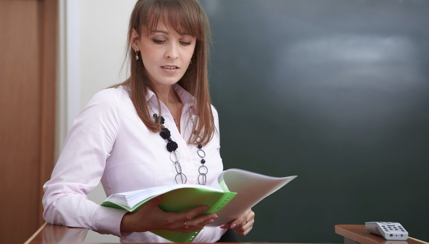 Student looking over notes at classroom podium
