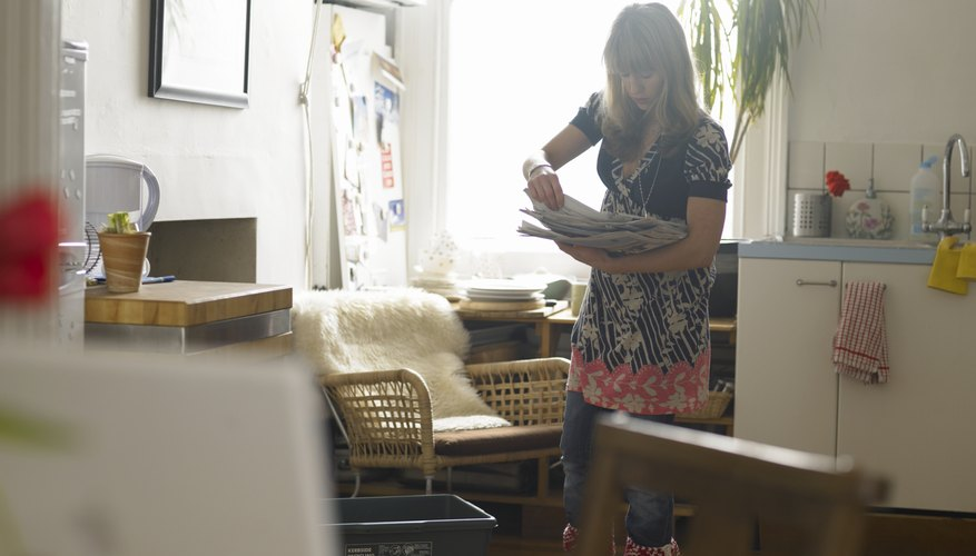 A woman recycles newspapers in her apartment.