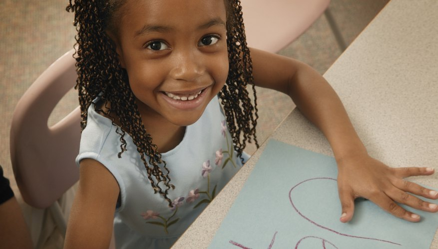 A young girl is drawing a picture.