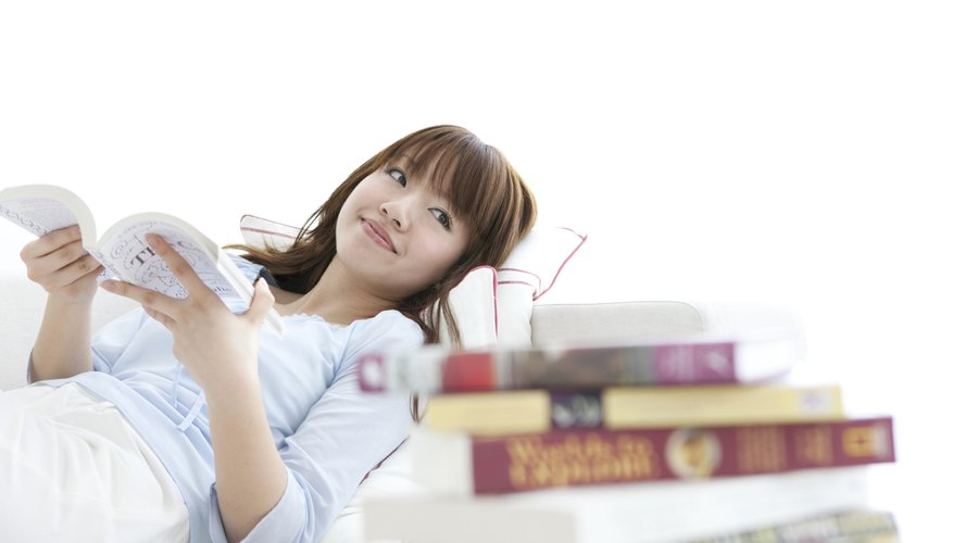 Young woman reading book in bed beside larger pile of books.