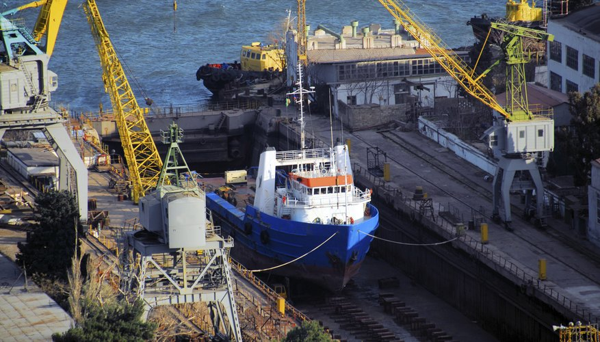 A ship is getting repaired in a dry dock.