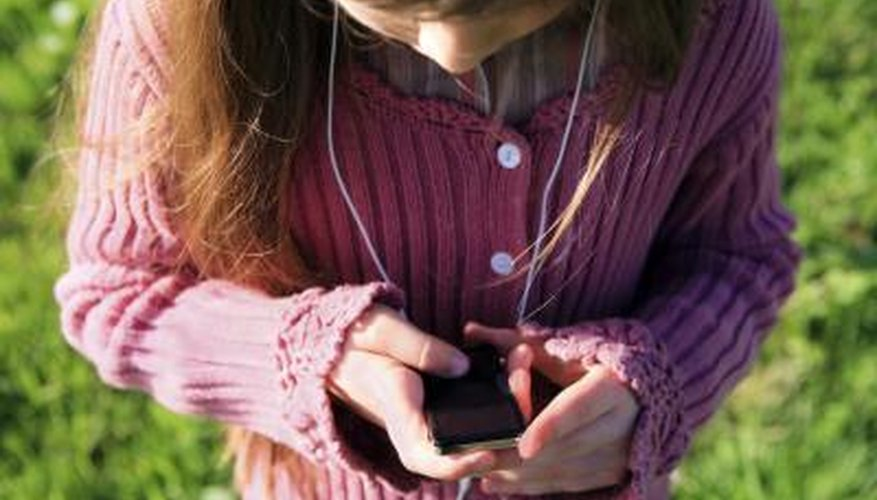 A girl listens to an mp3 player outside.