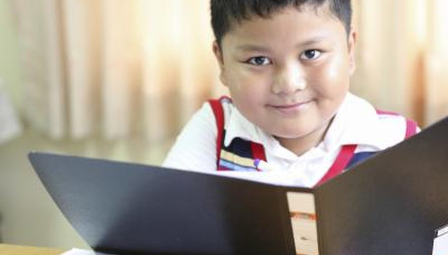 A school boy looks at documents in a binder.