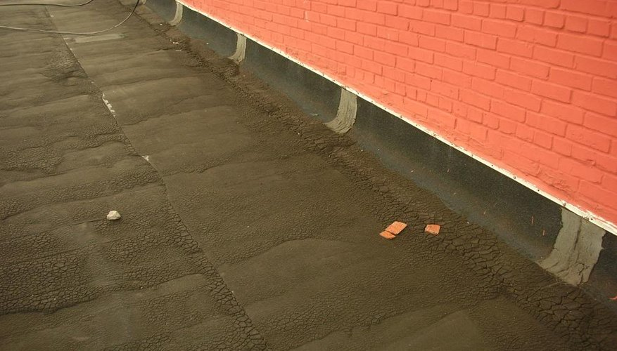 A brick wall next to an asphalt-covered roof.