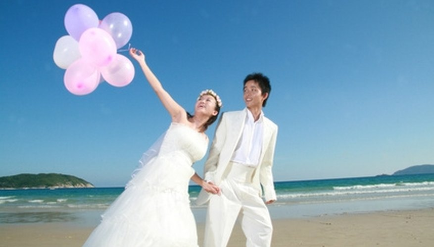 A bride and groom walk on the beach.