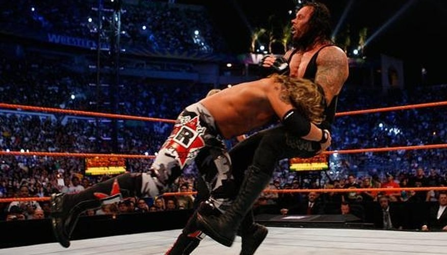 Edge performs a spear on the Undertaker.