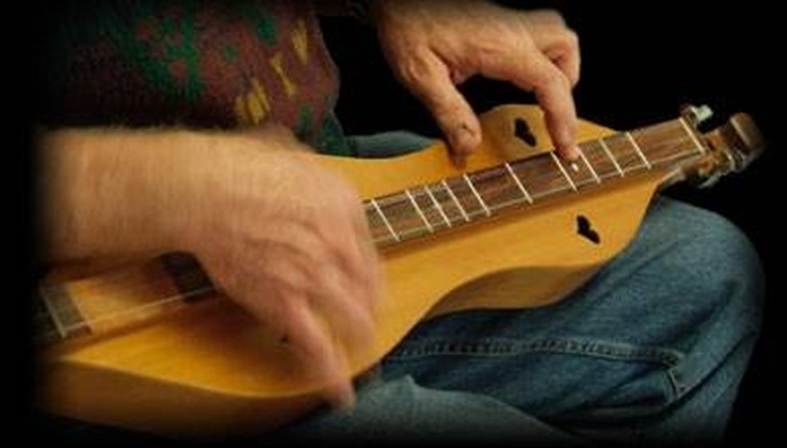 A man plays a finished mountain dulcimer