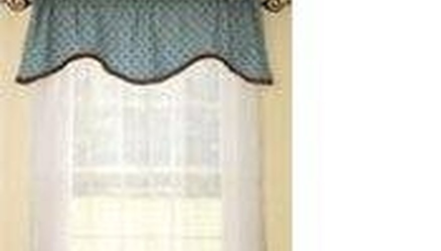 A shaped valance over sheer curtains.