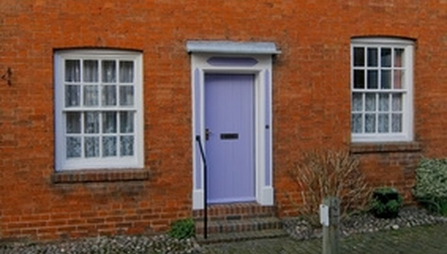 Windows installed within a brick house are fastened to an internal wooden frame or
