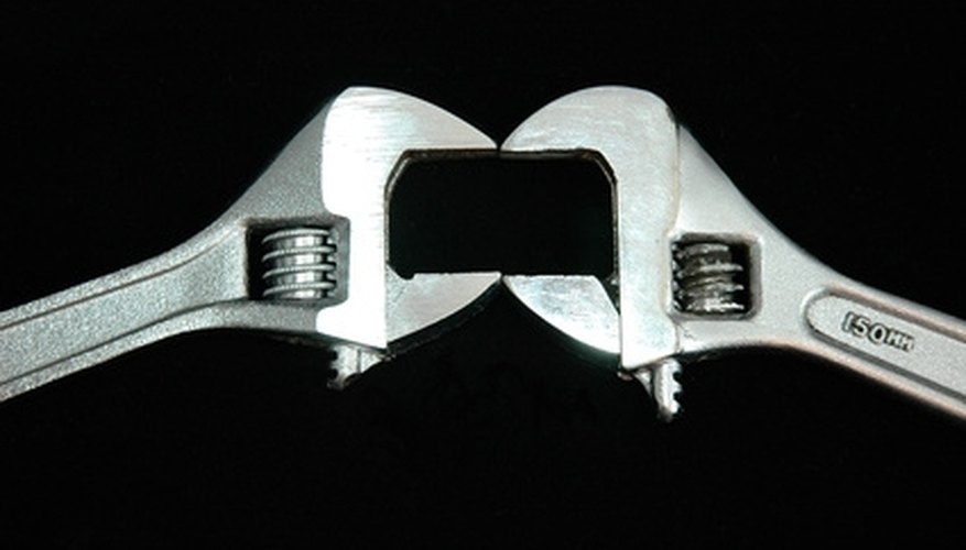 Use two wrenches to tighten hinge bolts with nuts attached.