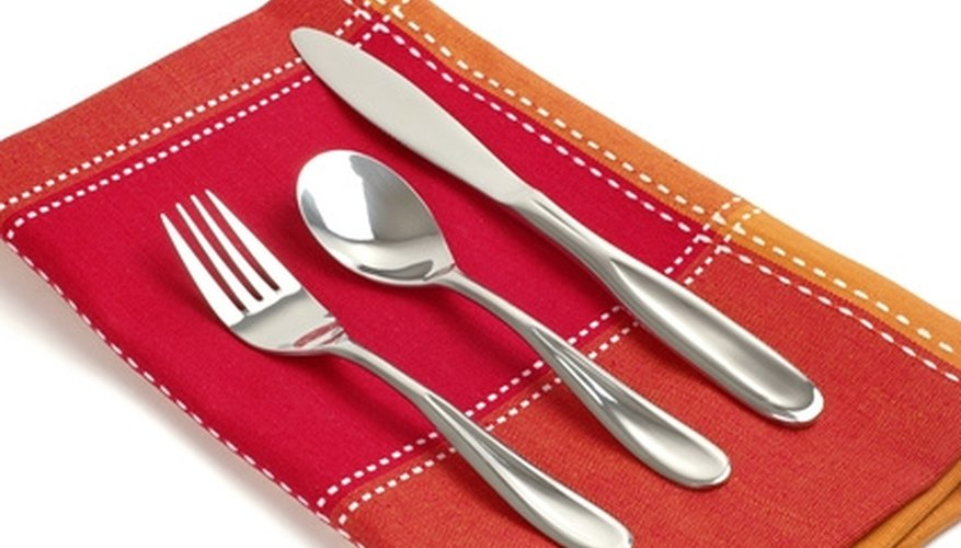 Flatware is marked to indicate composition and quality.