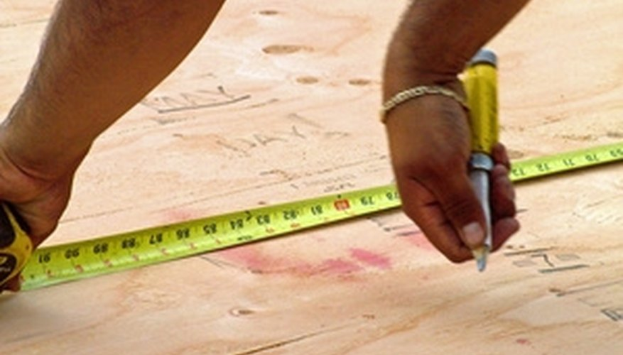 A man measures plywood sheating for the a house.