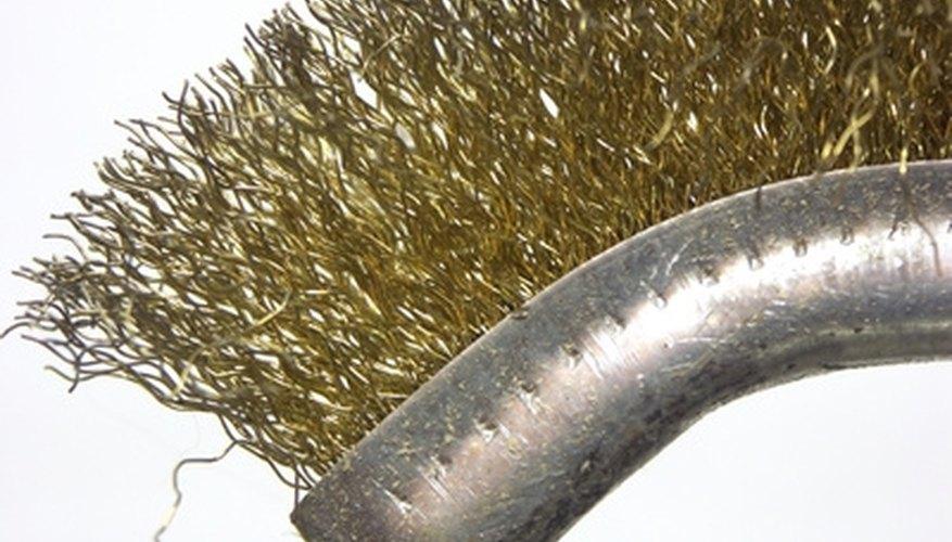 A stiff wire brush removes debris from the spark arrestor.