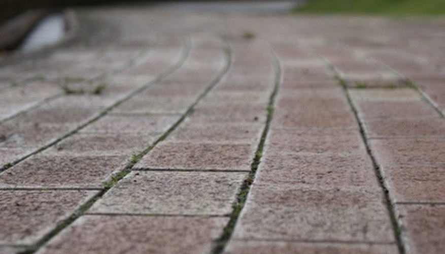 The white cloudiness on pavers should eventually disappear without any intervention.