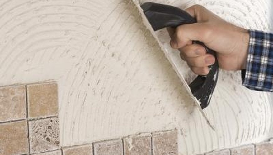 You must lay out and cut your tiles before applying adhesive.