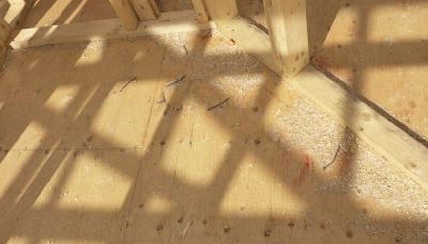 Seal a plywood floor with paint rollers.