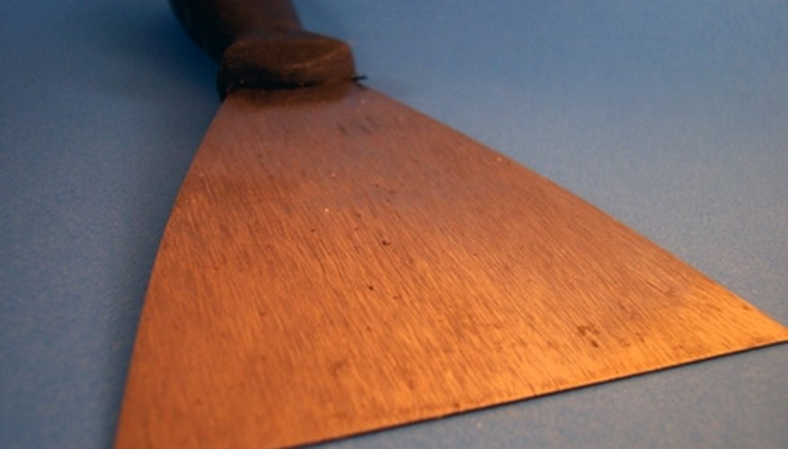 A hand scraper or putty knife allows demolition workers to scrape vinyl flooring from corners and tight spots.