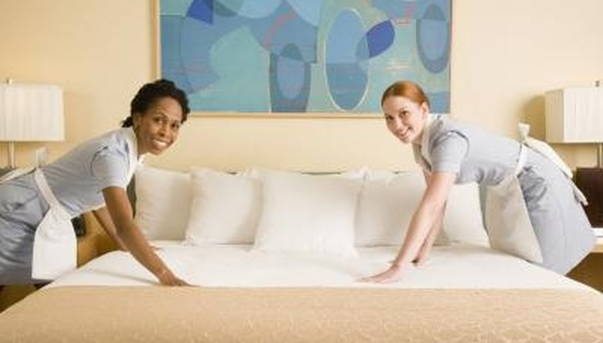 Maids smooth a finished bedspread.