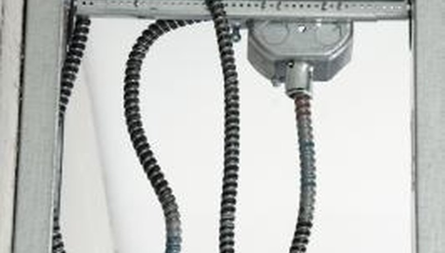 Metallic sheathed cables enter a junction box through holes called knockouts.