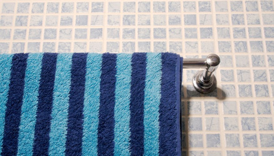 A towel bar is best positioned on a tile wall that is close to the shower.