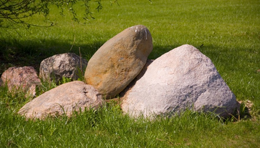 Partially buried and naturally arranged boulders provide interest and erosion control for a hill landscape.