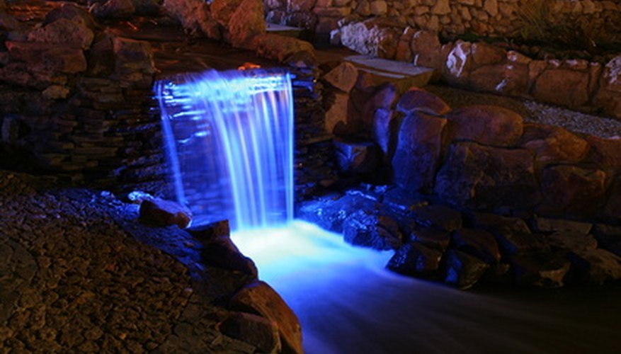 Lighting can enhance the soothing ambiance of a waterfall at night.
