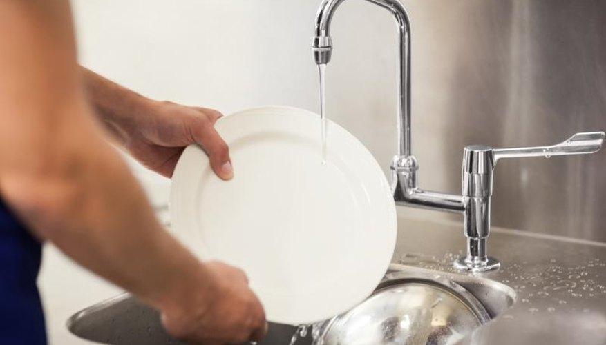 Busboy Washing Dishes In Sink.