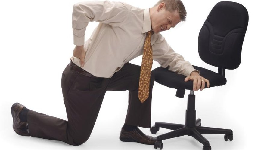 Man in pain sitting in conventional office chair.