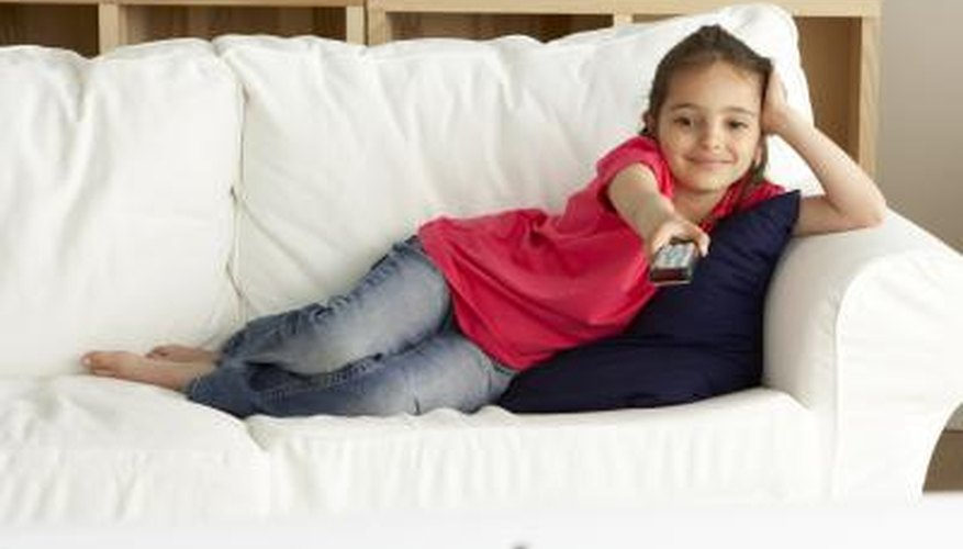 A girl watches TV on a sofa
