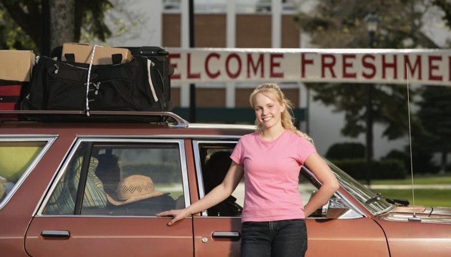 A freshman student arriving with bags on her car at college.
