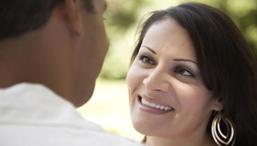 A woman smiles while listening to her partner.