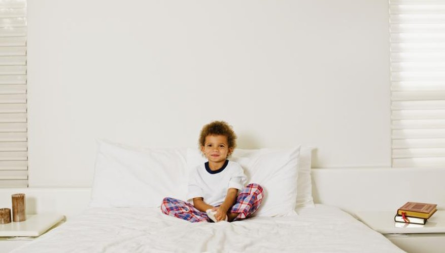 Small child sitting on bed