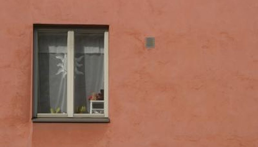 Stucco decorates the areas around the windows, but not the actual windows.