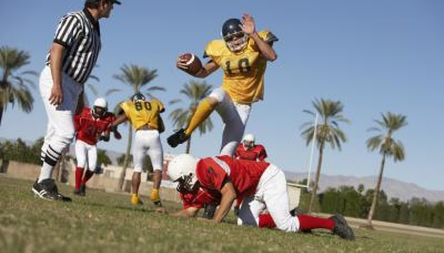 Football player jumping over a player.