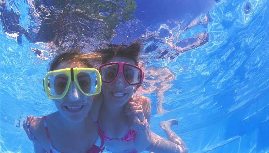 Tw young swimmers with googles smiling underwater.